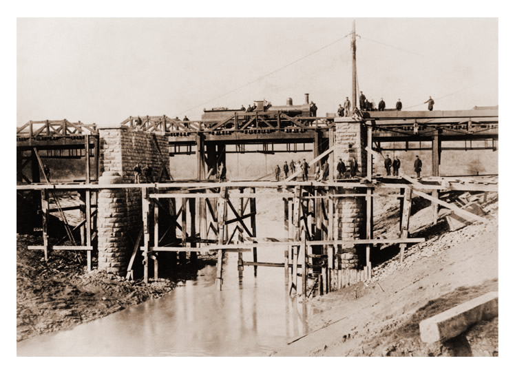The 'new' River Ely bridge with stone butresses is seen during construction with the original timber bridge to the rear.